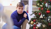 senior people : Chubby teen boy sitting in a chair near the Christmas tree. He looks at the toys, hang on the Christmas tree