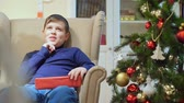 senior people : Chubby teen boy sitting in a chair near the Christmas tree. He is holding a gift in a red box