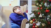 senior people : Young teen boy sitting in a chair near the Christmas tree. He looks at the toys, hang on the Christmas tree