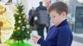 enfants jeux : Chubby teen boy stands in the mall. Christmas tree background. In the hands of holding a smartphone. He looks into it Vidéos Libres De Droits
