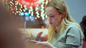 tasteful : Young teen girl writes smartphone message. She is having dinner in a cafe. Fast food, evening, on the background of light bulbs, bokeh Stock Footage