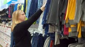 seçen : A woman in a clothing store chooses a shirt for her son