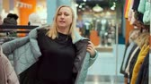 butik : A woman chooses a down jacket. In the outerwear store
