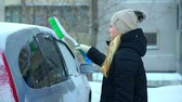 coberto : A young girl brushes her car of snow. Winter morning outdoors Stock Footage