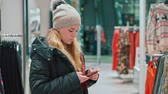 sklep : Young attractive girl looks into the smartphone. Shes in a clothing store, a mall Wideo