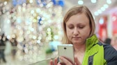 sklep : A woman is writing a message in a smartphone application, she is standing in a mall, with a light bulb in the background out of focus. Christmas mood