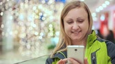 sehen : A woman is reading a smartphone message and smiling, she is standing in a shopping center, against a background of a light bulb, out of focus. Christmas mood Stock Footage