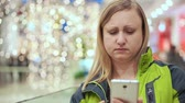 sklep : Woman reading a smartphone message and upset, depressed. She stands in a mall, amid a light bulb out of focus. Christmas mood Wideo