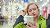 trabalhar fora : A woman straightens her hair, looking at the smartphone, she stands in a shopping center, against the background of a light bulb, out of focus. Christmas mood Vídeos