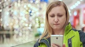 sklep : A woman reads a smartphone message and compresses lips. She stands in a mall, amid a light bulb out of focus. Christmas mood Wideo