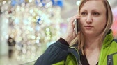 trabalhar fora : Woman talking on a smartphone, embarrassed and shy. She is standing in the mall, amid a light bulb out of focus. Christmas mood Vídeos