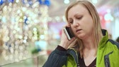 sklep : Woman talking on a smartphone and surprised. She is standing in the mall, amid a light bulb out of focus. Christmas mood Wideo