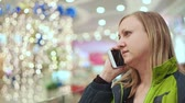 sklep : Woman talking on the smartphone. She is standing in the mall, amid a light bulb out of focus. Christmas mood