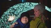 defocused 표시 : Boy and mother on the street, New Years Eve. They hold a sparkler and rejoice