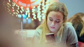 tasteful : Young teen girl read smartphone message. She is having dinner in a cafe. Fast food, evening, on the background of light bulbs, bokeh