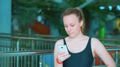 apartamentos : A young girl in a black swimsuit is looking at your smartphone.