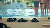 stopy : Many slippers on the shore of an indoor aqua park. Defocused background