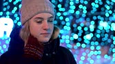 female cell : A young attractive girl in a hat, in the winter outside stands on a background of blue lights. Christmas and New Year come