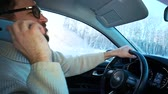 se movendo para cima : A man drives a car in winter on the highway between cities. He is talking smartphone and laughing
