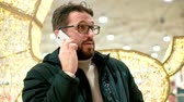 스웨터 : Bearded man in glasses is talking on a smartphone.