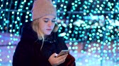 female cell : Young attractive girl in a hat uses a smartphone in the winter on the street. She stands against the blue lights and reads a text message. Christmas and New Year come Stock Footage