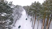 zasněžený : Aerial view of the car moving in the winter forest. The drone flies over the trees