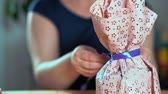 envolto : Close-up of a womans hand packing a gift. Purple packing tape