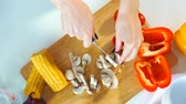 ingredienti : Top view close-up of a young woman cutting vegetables in the kitchen with a knife on the table. She cuts fresh mushrooms. Next is fresh corn and red pepper