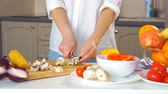 ingredienti : Close-up of a young woman cutting vegetables in the kitchen with a knife on the table. She cuts the fresh mushrooms on the chopping Board. Filmati Stock