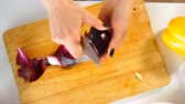sporák : Top view of a young woman cuts the red onion. On the table next to the vegetables, making vegetable salad