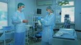 medical gown : Timelapse surgical nurse helps the doctor to wear a bathrobe in the operating room Stock Footage