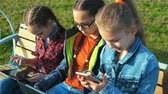 group of children : City scene, three children girls sitting on a bench. They look at tablets and smartphones. Stock Footage