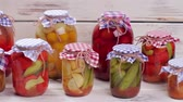 przetwory : Glass jars with canned vegetables and fruits on a wooden shelf. Canned foods.