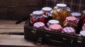 konserve : Glass jars with preservation in an old suitcase. Wooden shelves of old boards.