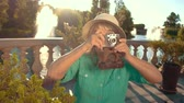 célzás : Mature woman holding camera. Lady in summer hat. Grandma at the resort. Photographer gives hints. Stock mozgókép