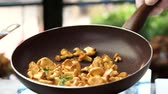 cantharellus : Flipping food in a pan. Chanterelles with garlic and rosemary. Stock Footage