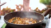 cantharellus : Mushrooms frying in slow-mo. Chanterelles and herb.