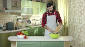 cucumber soup : Man cutting tomato. Bearded guy wearing apron. Easy and tasty soup recipes. Stock Footage