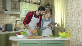 recipe : Couple with tablet cooking. Woman and man, vegetables. Find recipes in the internet.