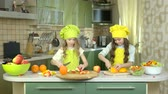 recipe : Little girls cutting fruit. Oranges and apples.