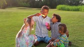 paseka : Four children are playing on the evening glade. They are making soap bubble and catching its.