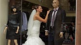 obrączki : Bride standing in showcase boutique with a mannequin.