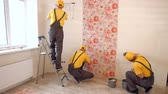 laminate : Brigade of builders hang wallpaper in the apartment. Masters make repairs.