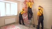 parke : Specialists wallpapering in the house. Brigade of craftsmen making renovation.