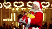 kind : Santa Claus holding presents. Happy Santa showing thumb up.