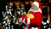 kind : Happy Santa Claus holding gifts. Santa showing thumb up.