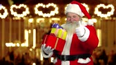 kolotoč : Santa is showing thumb up. Santa Claus holding present boxes.