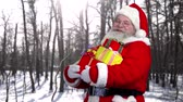 kciuk w górę : Santa with presents outdoor. Happy Santa Claus, forest background.