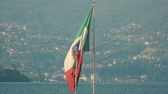 военно морской : Italian flag on Stresa background. Flag, water and town. Стоковые видеозаписи