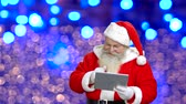 hélio : Santas wishing merry Christmas through the tablet. Santa with tablet in front of a blue background.